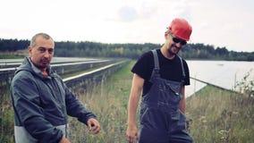 De ingenieur bespreekt met een mens het werk van de zonnebatterij stock footage