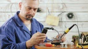 De ingenieur is bezig geweest met reparatie van de oude mobiele telefoon stock footage