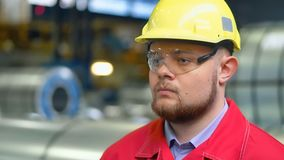 De ingenieur in bouwvakker beweegt zich door een zware industriefabriek stock footage