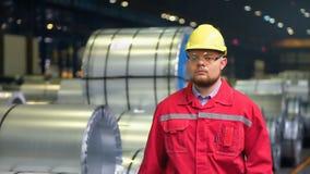 De ingenieur in bouwvakker beweegt zich door een zware industriefabriek stock video