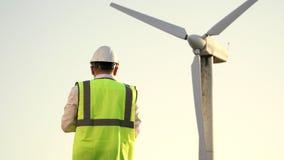 De ingenieur in bouwvakker en helder vest is dichtbij de windmolen en het letten op om te zien hoe het werkt stock videobeelden