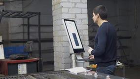 De ingenieur controleert computerpc die scherp metaal bij de industriële vervaardiging stock video