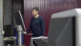 De ingenieur controleert computerpc die scherp metaal op metallurgische installatie stock footage