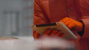 De ingenieur controleert de documenten op tablet binnen nieuw modern de industriepakhuis