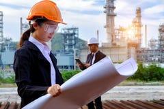 De ingenieur controleert een lay-out met grote de industrieachtergrond royalty-vrije stock foto