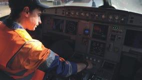 De ingenieur controleert het materiaal in de cockpit van een passagiersvliegtuig 4K stock videobeelden