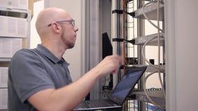 IT de ingenieur controleert het serverrek stock footage
