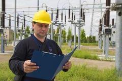 De ingenieur controleert hoogspanningstransformerstation Stock Foto