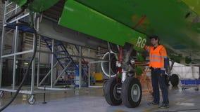 De ingenieur controleert de verrichting van het broedsel van het voor landingsgestel van de vliegtuigen stock videobeelden