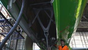 De ingenieur controleert de verrichting van het broedsel van het voor landingsgestel van de vliegtuigen stock video
