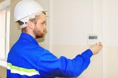 De ingenieur in de witte helm plaatst de temperatuur op het controlebord van de airconditioner Stock Foto