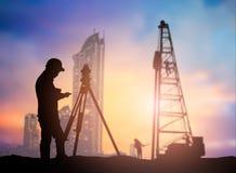 De ingenieur die van het silhouetonderzoek in een bouwterrein over Blurr werken Stock Fotografie