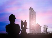 De ingenieur die van het silhouetonderzoek in een bouwterrein over Onduidelijk beeld werken Stock Foto's