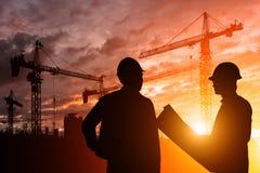 De ingenieur die van silhouetteams bouwvakker in een bouwterrein zonsondergang bekijken Stock Afbeelding