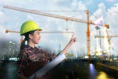 De ingenieur die van vrouwenazië en blauwdrukken werken houden bij constructi Stock Afbeelding