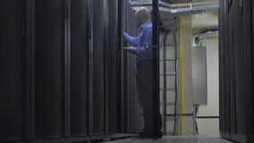 IT de ingenieur in een blauw overhemd met een blocnote, opent het serverkabinet in serverruimte stock videobeelden