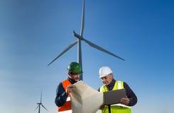 De ingenieur en de geoloog raadplegen dicht bij windturbines in het platteland stock foto