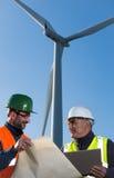 De ingenieur en de geoloog raadplegen dicht bij windturbines in het platteland stock fotografie