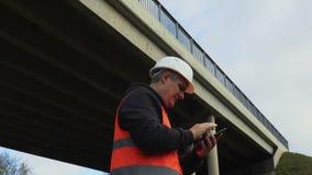 De ingenieur filmde met tabletpc beschadigde brug stock videobeelden