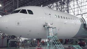 De ingenieur herstelt de deur van een passagiersvliegtuig Het vliegtuig in de deurreparatie 4K stock videobeelden