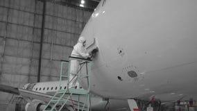 De ingenieur herstelt de deur van een passagiersvliegtuig Het vliegtuig in de deurreparatie 4K stock footage