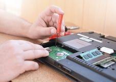 De ingenieur herstelt laptop PC Het installeren van de harde aandrijvingshardware, RAM Elektronische reparatiewerkplaats, technol stock fotografie