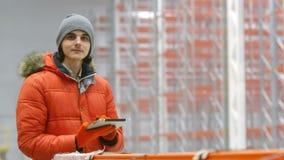 De ingenieur kijkt naar de tablet en op de kanten binnen een nieuw modern pakhuis stock footage