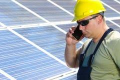 De ingenieur is maakt vraag met een mobiele telefoon in zonneelektrische centrale Royalty-vrije Stock Foto