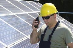 De ingenieur is maakt vraag met een walkie-talkie in zonneelektrische centrale Stock Fotografie