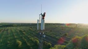 De ingenieur met gadget verbond een mobiel communicatiemiddel over radiotelecommunicatietoren op achtergrond van blauwe hemel aan