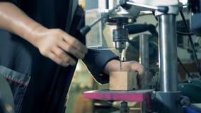 De ingenieur met prothetische handen werkt bij een fabriek, die een houten bar boren 4K
