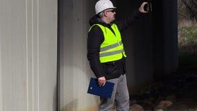 De ingenieur neemt beelden op lijstpc dichtbij brugbouw stock video