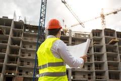 De ingenieur op bouwterrein onderzoekt blauwdrukken Royalty-vrije Stock Foto's
