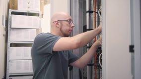 IT de ingenieur opent het de serverrek en controles stock video