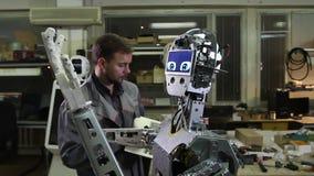 De ingenieur past de robot aan stock footage