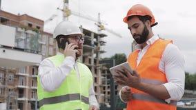 De ingenieur spreekt op Mobiele telefoon op bouwwerf en controleert het werk van de arbeider Bouwersbesprekingen op smartphone stock videobeelden