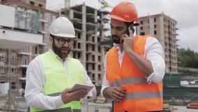 De ingenieur spreekt op Mobiele telefoon op bouwwerf en controleert het werk van de arbeider Bouwersbesprekingen op smartphone stock video