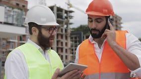 De ingenieur spreekt op Mobiele telefoon op bouwwerf en controleert het werk van de arbeider Bouwersbesprekingen op smartphone stock footage