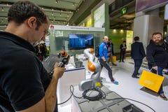 De ingenieur stelt industriële KUKA-robot in cabine van Huawei-bedrijf in werking Royalty-vrije Stock Foto's