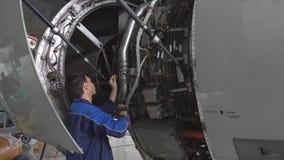 De ingenieur, technicus onderzoekt de straalmotor met een flitslicht stock videobeelden