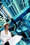 De ingenieur van de vrouw tegen pijpen Royalty-vrije Stock Afbeelding