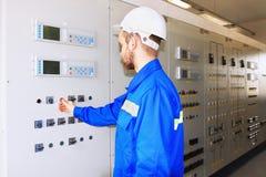 De ingenieur van een industrieel machtsbedrijf in witte helm drukt starter op het controlebord stock foto