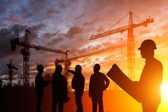 De ingenieur van silhouetteams in een bouwterrein bij zonsondergang Stock Foto's