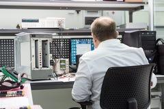 De ingenieur voert een test van de gebeëindigde elektronische modules uit Laboratorium voor het testen en aanpassing van elektron royalty-vrije stock foto's