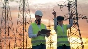 De ingenieur in VR-glazen werkt bij bouwwerf, terwijl een elektricien op een tablet typt stock videobeelden