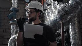 De ingenieur werkt in ketelruim en dicteert audiobericht op smartphone stock videobeelden