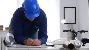 De ingenieur Working in Bureau analyseert en bestudeert Plannen en Projecten stock video