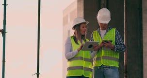 De ingenieurs of de architecten hebben een bespreking bij bouwwerf kijkend door het plan van bouw contre jour stock video