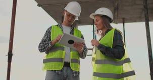 De ingenieurs of de architecten hebben een bespreking bij bouwwerf kijkend door het plan van bouw contre jour stock footage