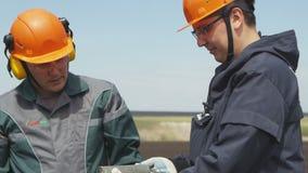 De ingenieurs in eenvormig en handschoenen onderzoeken gehaalde kern terwijl het boren stock video